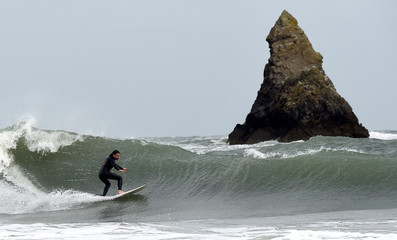 A surfer attempts to ride large waves near Broad Haven