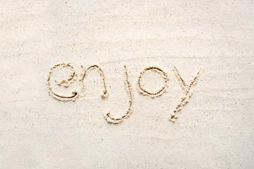 "Handwriting words ""Enjoy"" on sand"