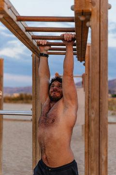 Strong man climbing horizontal ladder