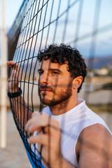 Bearded sportsman near volleyball net