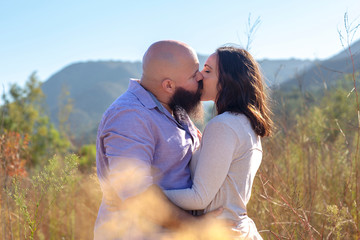 Close up of couple kissing in grass field overlooking mountains