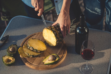 cropped view of woman cutting pineapple and avocados on wooden board near bottle of red wine