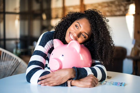 Black woman hugging her piggy bank