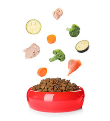 Fresh ingredients falling into bowl with dry pet food for cats and dogs on white background