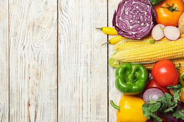 Flat lay composition with assortment of fresh vegetables on wooden background. Space for text
