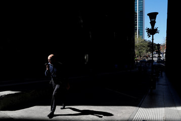 A man talks on his cellphone as he walks in Buenos Aires' financial district