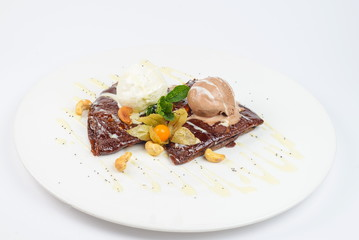 chocolate pancakes with ice cream on a white plate
