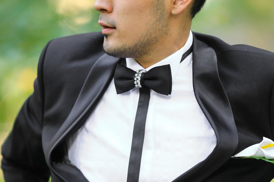 groom, a man in a black jacket, a white shirt and a bow tie