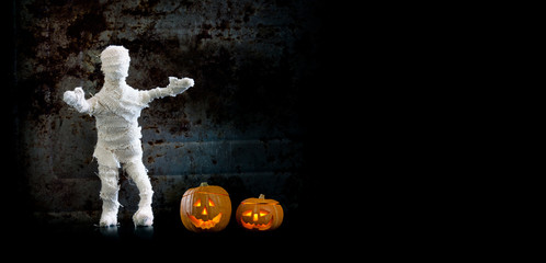 Halloween background scary mummy character orange pumpkins on vintage wall. Copy space