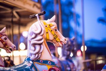 Brilliant vintage merry-go-round wooden horses against the background of Children's Carousel at night time.