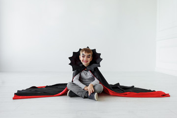 Laughing halloween boy with bat like collar for posters