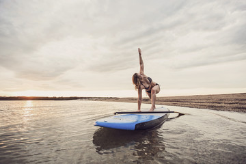 Fit young woman doing yoga on paddleboard