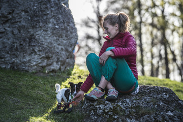 Woman sitting on rock and playing with dog