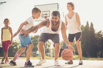 Family playing basketball together.