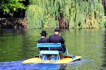 2 Hasidic Jews in traditional black clothes ride a catamaran on the lake in the autumn Sophia Park in Uman, Ukraine,