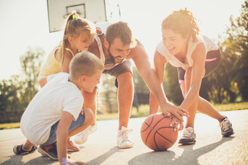 Family outside playing basketball together.