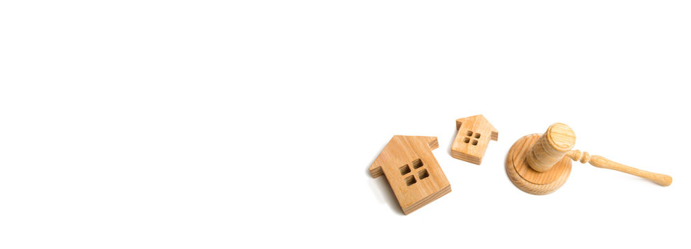 concept of court cases on property and real estate. Confiscation and nationalization, confirmation of tenure rights. Two wooden houses and a hammer of the judge on a white background Banner copyspace