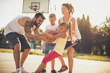 Girls will win. Happy family playing basketball. Moving activity.