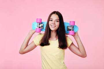 Young girl with skateboard on pink background