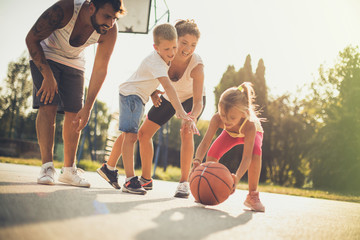 Young parents playing basketball together.