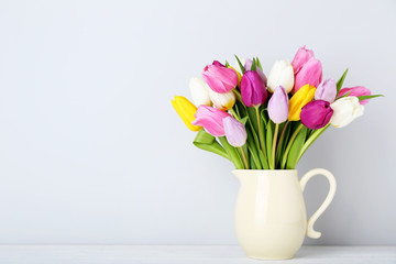 Bouquet of tulips in jug on wooden table