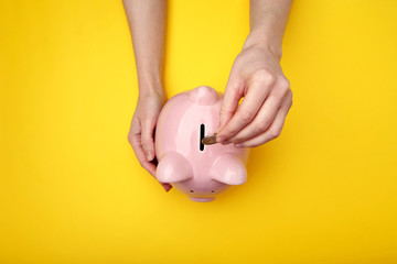 Female hand putting coin into piggy bank on yellow background