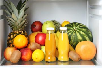 Open fridge full of fruits and bottles of juice