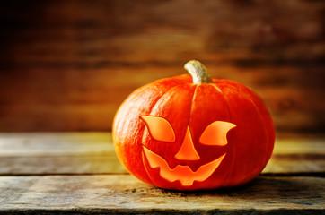 Glowing pumpkin on dark wood background