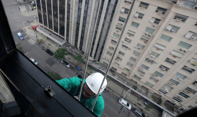 Worker wears a helmet as he cleans the window of an office building in downton of Rio de Janeiro