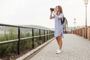Outdoor summer lifestyle portrait of pretty young woman having fun in the city in Europe in evening with camera travel photo of photographer Making pictures in hipster style
