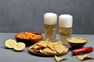Two glasses of light beer and snacks. On the plates, peanuts in a crispy spicy crust, corn chips nachos, Mexican guacamole sauce. Next to the plates are two halves of lime. Gray background.