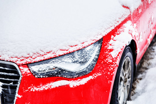 The headlight of a red car covered with snow.