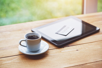 coffee cup and digital tablet with credit card. online shopping and paying