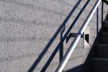 steel railing casting shadows on plastered wall