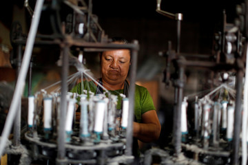 A worker processes recycled plastic to make hats at The Pichinte Hat Makers in Cojutepeque