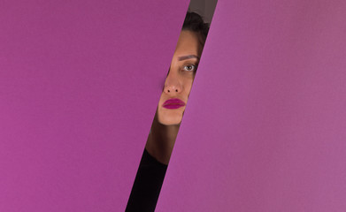 A girl is looking in a hole of colored paper.