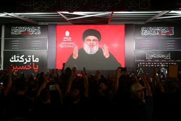 Lebanon's Hezbollah leader Sayyed Hassan Nasrallah gestures as he addresses his supporters via a screen the night before Muslim Shi'ites around the world mark the day of Ashura, in Beirut