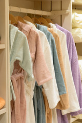 Modern bathrobe clothes collection hang on a shelf in a designer clothes store. Lifestyle home living concept.