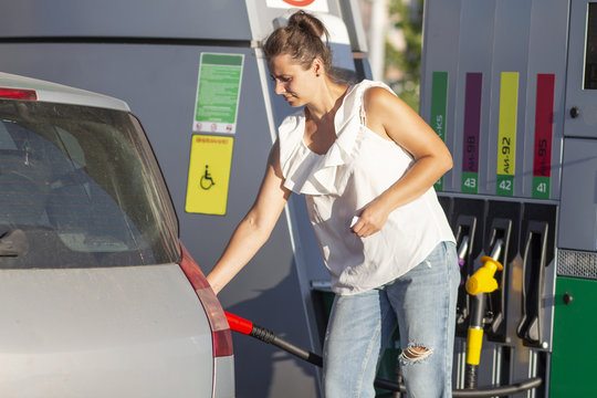 Woman at gas station. The girl pours fuel into the tank of the machine at the fuel station