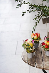 Roses and green leaves in buckets on a wooden table