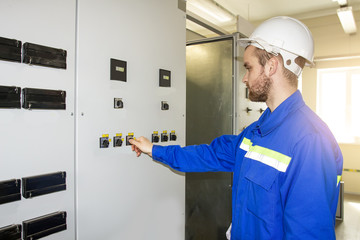 Worker on the control panel of industrial equipment. Automation of production. Electric engineer in the closet of protection and automation. Operation of electrical installation