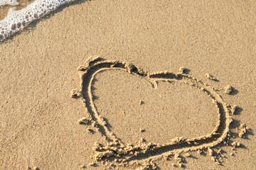 drawn heart on wet sand near the sea