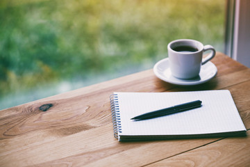 cup of fresh morning coffee with paper notebook and pen for writing