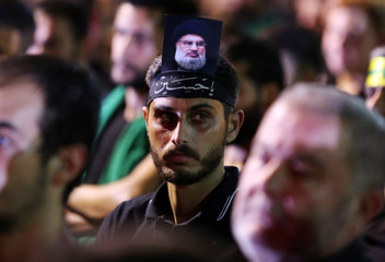 A supporter of Lebanon's Hezbollah leader Sayyed Hassan Nasrallah has his picture on his head, during a live broadcast, the night before Muslim Shi'ites around the world mark the day of Ashura, in Beirut