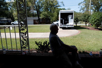 Bob Gantt, 88, takes a breather on his carport while removing the contents of the home he shares with his wife Virginia before flood waters arrive in the aftermath of Hurricane Florence now downgraded to a tropical depression in Conway