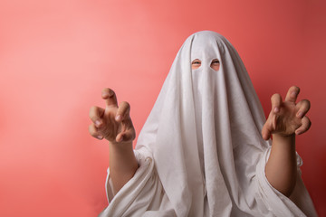 young child dressed in a ghost costume for halloween on pink background