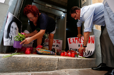 Activists place photos of assassinated anti-corruption journalist Caruana Galizia together with flowers, candles and protest posters, in the entrance of Malta's Ministry of Justice in Valletta
