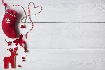 Christmas wooden white background, red sock, reindeer and red berries