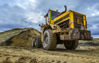 excavator working on sand dunes, cloudy day, beautiful storm clouds, bottom view, point of view