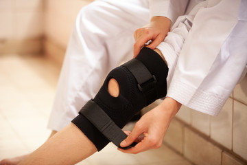 leg with one knee in a protective knee brace